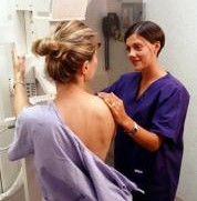Technician and patient at mammogram machine