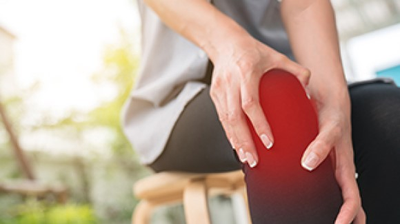 woman grabbing knee with red color to  indicate pain