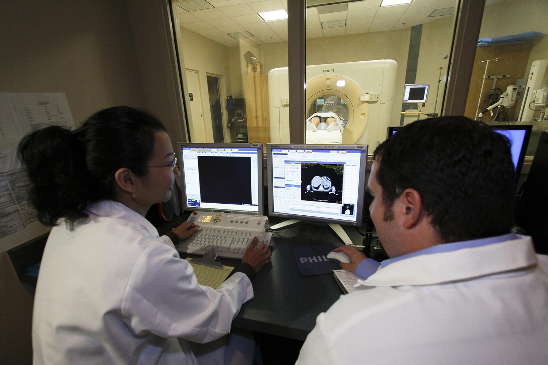 Esta es una foto de dos radiólogos observando una imagen de TC en una computadora mientras se realiza el escaneo