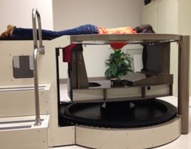 Esta es una foto de una mujer recostada en la parte superior de un escáner de TC de seno dedicado