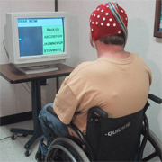 Man in a wheelchair using the brain computer interface cap that captures brain waves and allows him to move a computer curser using his thoughts. Photo Credit: Dr. Jonathan Wolpaw, Wadsworth Center, Albany, NY
