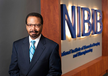 image of Dr. Roderic Pettigrew standing in front of NIBIB sign outside the NIBIB office suite.