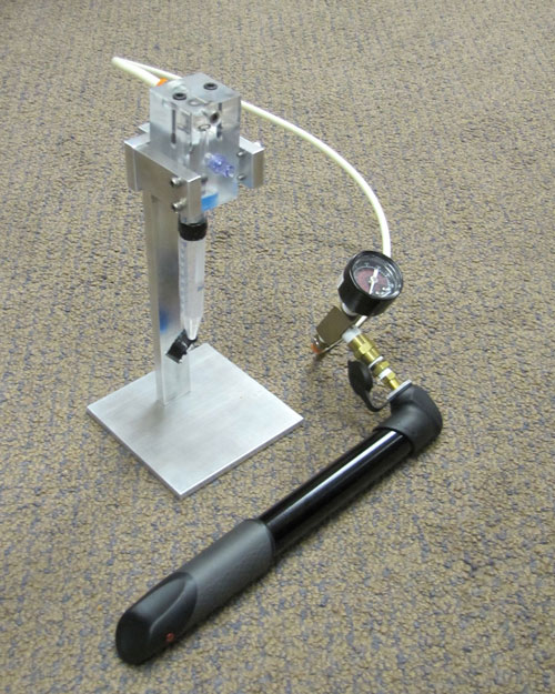 "Running on mechanical pressure provided by a bicycle pump, this portable system extracts RNA from a patient's blood sample and stores it on a sample stabilization ""straw."" Stored samples will not require a cold chain of transportation. The device will be useful in monitoring the status of HIV infection. Image provided courtesy of Catherine Klapperich, Ph.D., Boston University."
