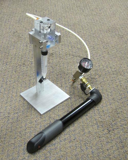 """Funcionando por presión mecánica proporcionada por una bomba de bicicleta, este sistema portátil extrae ARN de una muestra de sangre de un paciente y lo guarda en una """"paja"""" de estabilización de la muestra. Las muestras almacenadas no requerirán de una cadena fría de transporte. El dispositivo será de utilidad en el seguimiento del estado de la infección por VIH. Imagen suministrada por cortesía de Catalina Klapperich, Ph.D., Universidad de Boston."""