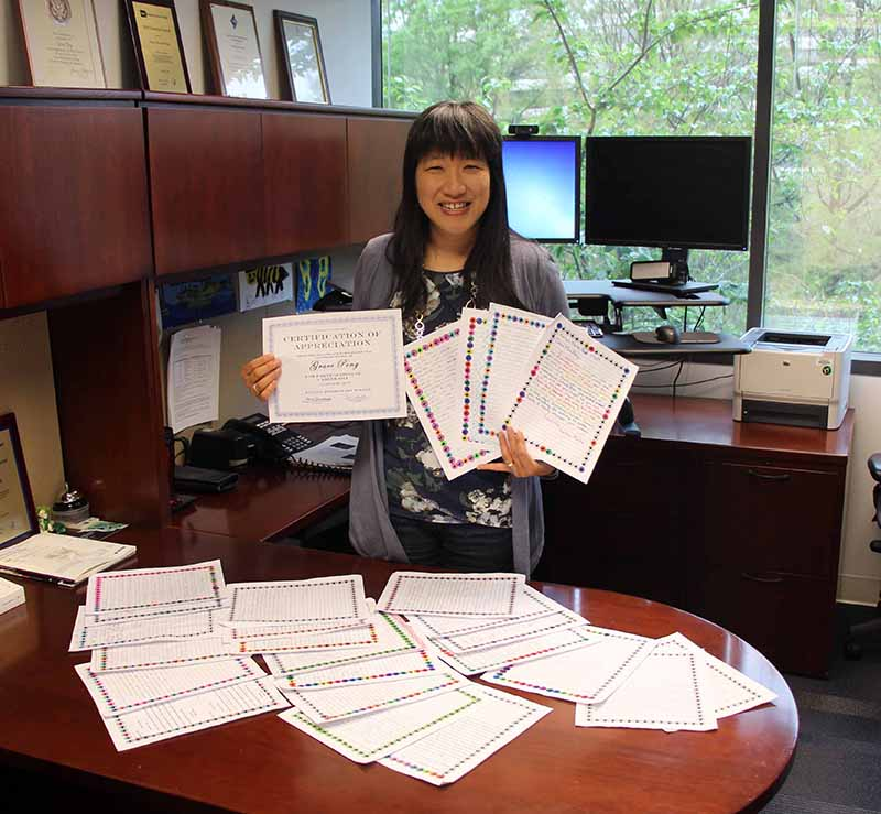 Grace Peng displays Certificate of Appreciation and thank you letters from students at Fulton Elementary School, Fulton, Maryland.