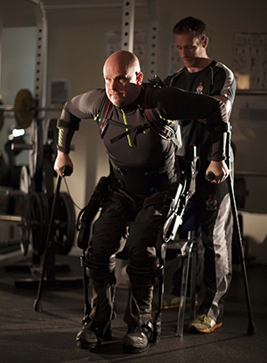 Mark Pollock, a 39-year-old man with a complete spinal cord injury so that he is paralyzed from the waist down, rises to a standing position in an exoskeleton. The device and transcutaneous spinal stimulation assisted him in taking steps during a clinical study at UCLA.