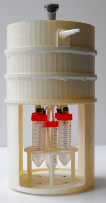 A photo of the microflora refinement system, a white bin with three tubes with red caps attached to the bottom spout.