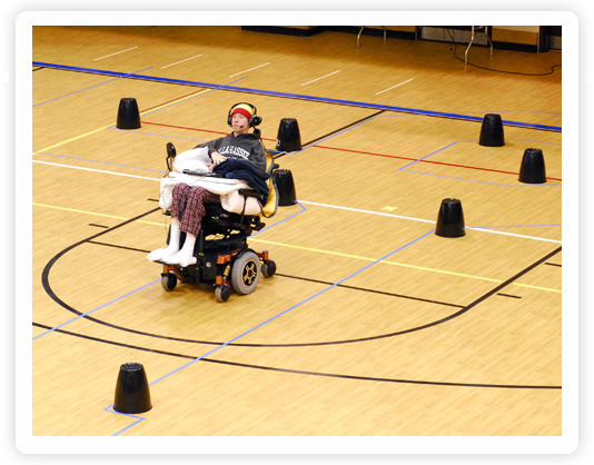 Photo of a man using the tongue drive wheelchair moving through black obstacles on the ground