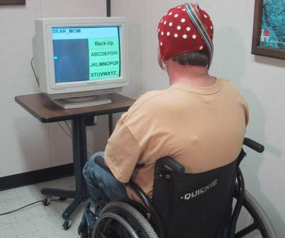 Foto de un hombre en silla de ruedas sentado frente a una computadora con una gorra roja con electrodos EEG
