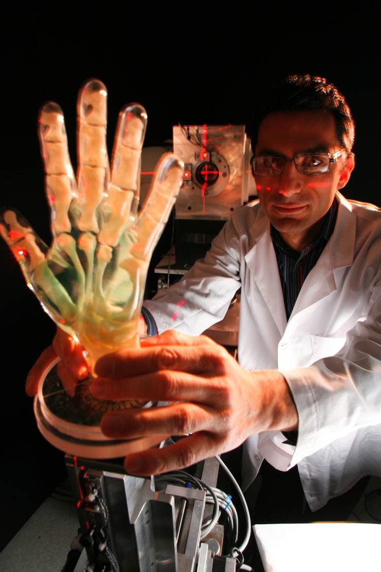 A photo of a researcher holding a transparent robotic hand with wires running through it
