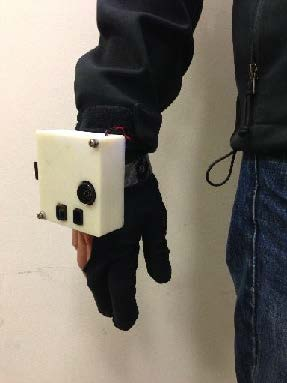 A photo of a gloved hand with a white box attached to the back.