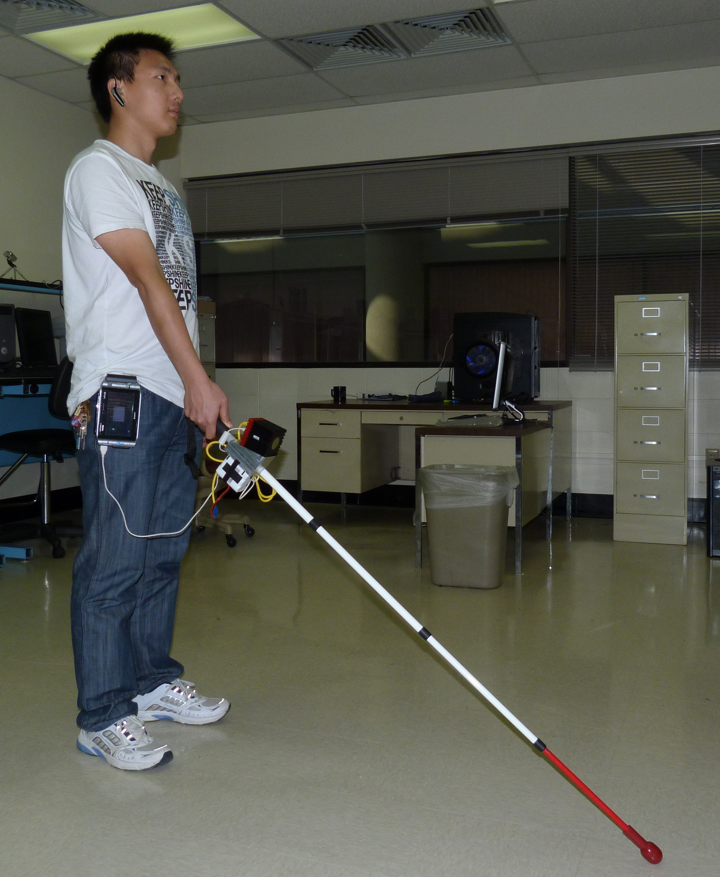 This is an image of a person holding the prototype of the co-robotic cane.