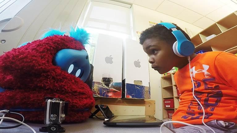 Photo of a preschooler interacting with the social robot companion.