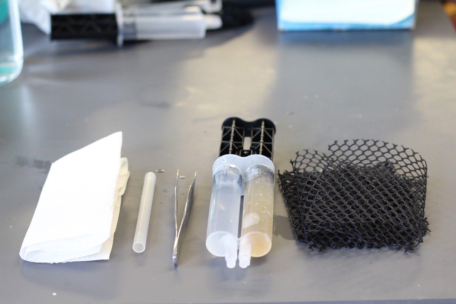 A photo of the GelAid components, including a tube, dual tubes with liquid in one and gel in the other, tweezers, and a black netting