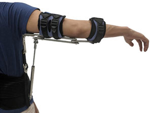 A man's arm is being held straight out to his right by metal connected to straps on his arm and a waist band.
