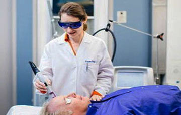a nurse doing a cosmetic laser treatment with a patient - Biophotonic