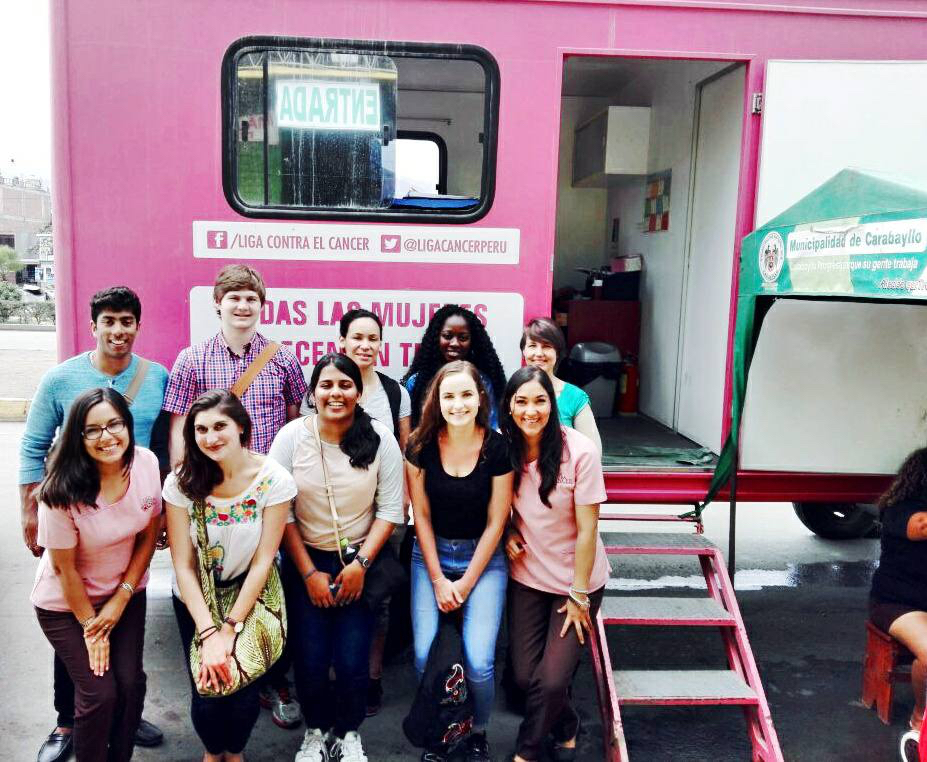 students standing in front of pink van