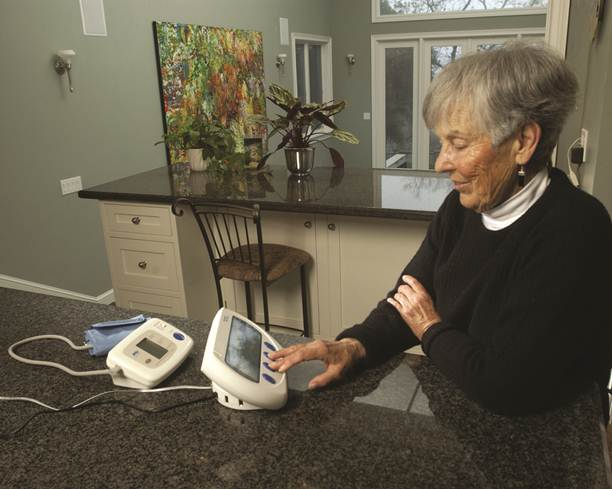 Photo of an elderly woman touching a small device connected to a blood pressure band