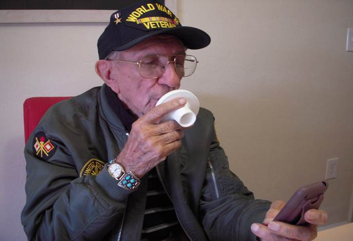 A photo of an elderly man bringing a small, circular, plastic device to his mouth.