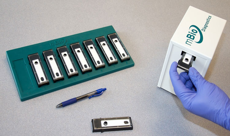 A photo of small chip devices on a desk next to a pen for scale and a purple gloved hand placing one of the devices into a box labeled mBio Diagnostics