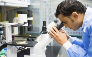 male scientist in a lab looking into a microscope