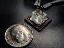 A photo of a small electronic device next to a dime to show scale